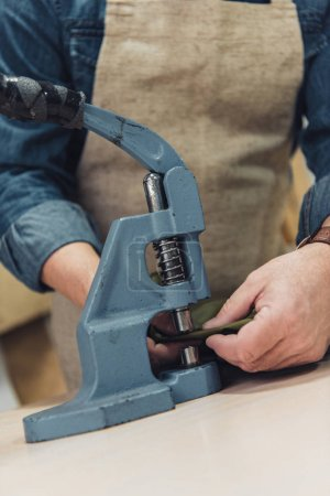 cropped image of male handbag craftsman working with tool at studio