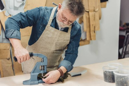 concentrated mature male handbag craftsman working with tool at studio