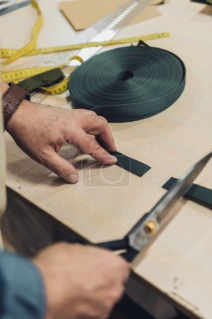 cropped image of male handbag craftsman cutting fabric by scissors at workshop