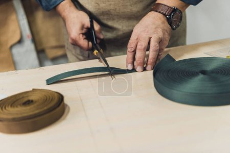 partial view of male handbag craftsman cutting fabric by scissors at workshop