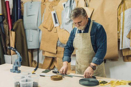 middle aged male handbag craftsman in apron and eyeglasses working with fabric at studio