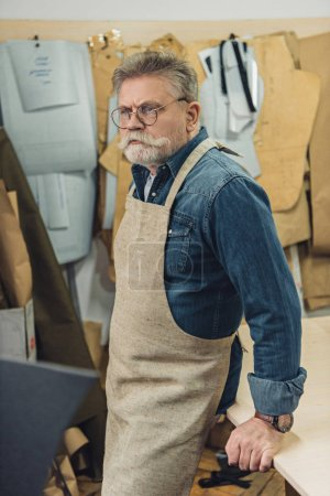 confident middle aged male craftsman in apron posing at workshop