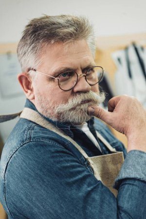 pensive middle aged male craftsman in apron posing at workshop