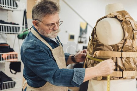 mature male tailor making measurements on military vest at workshop