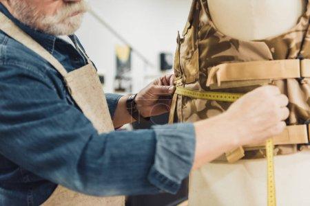 Foto de Imagen recortada de sastre masculino maduro haciendo mediciones en chaleco militar en taller - Imagen libre de derechos