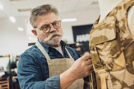 focused middle aged male tailor making measurements on military vest at workshop