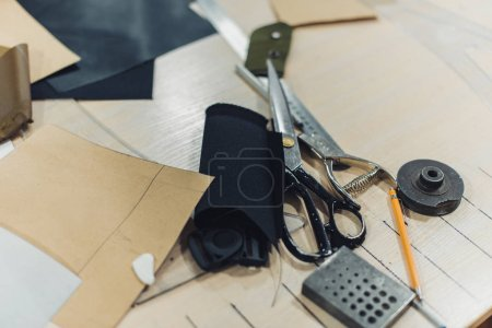 selective focus of tailor workplace with scissors and fabric at studio