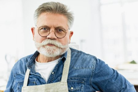 portrait of middle aged male craftsman in apron posing at workshop