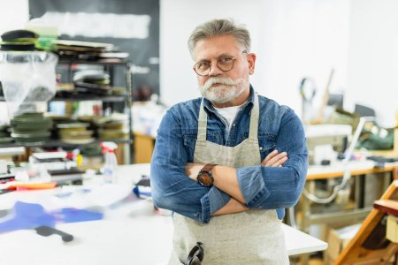 mature male craftsman in apron posing with crossed arms at workshop