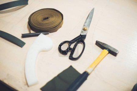 close up view of working table with fabric, hammer and scissors at workshop