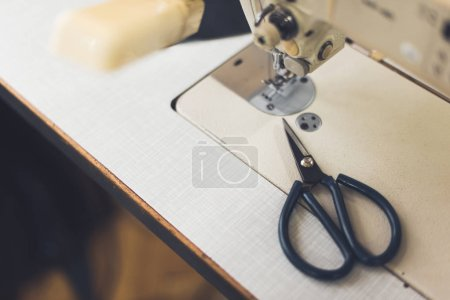 selective focus of sewing machine and scissors at workshop