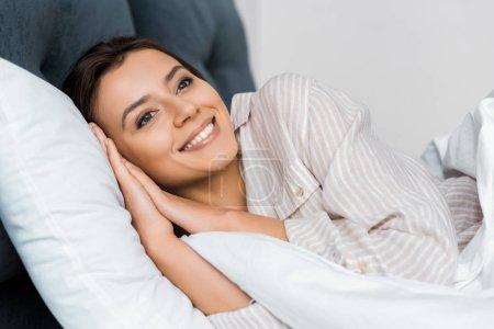 Photo pour Belle jeune fille souriante en pyjama détente dans son lit - image libre de droit