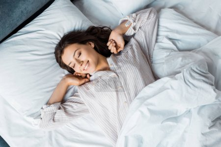 Photo for Attractive young woman in pajamas waking up in bed in the morning - Royalty Free Image