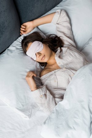 attractive young woman sleeping in eye mask in bed