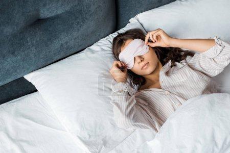 jeune femme en sommeil masque réveil dans son lit le matin