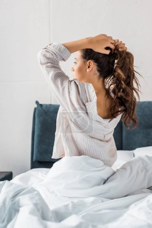 Photo for Brunette woman making pony tail while sitting on bed in the morning - Royalty Free Image