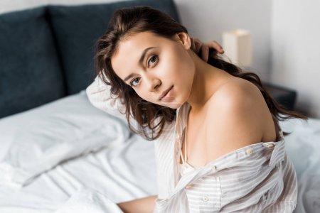 Foto de Hermosa mujer tierna mirando a cámara y sentado en la cama por la mañana - Imagen libre de derechos
