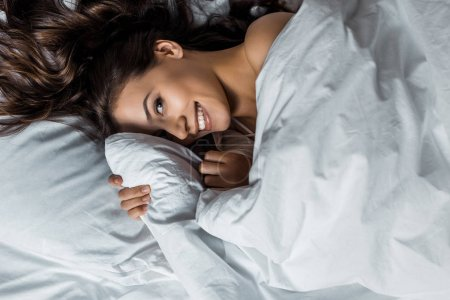 beautiful cheerful girl hiding under white blanket on bed