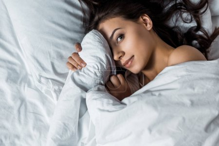 brunette girl looking at camera and hiding under white blanket on bed