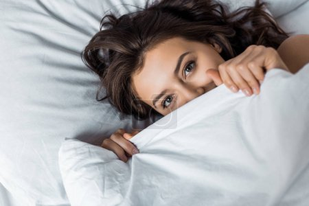 beautiful happy woman hiding under white blanket on bed