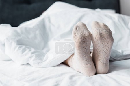 Photo for Cropped view of girl in socks lying under white blanket in bed - Royalty Free Image