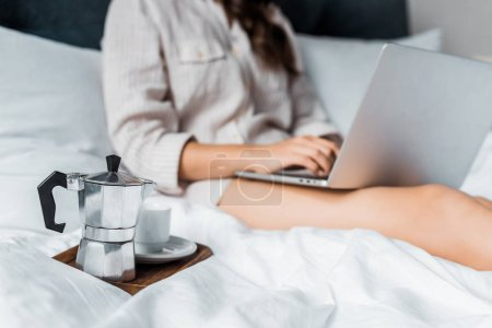 selective focus of moka pot with coffee cup and woman with laptop in bed