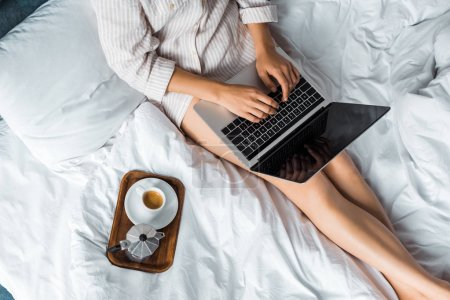 cropped view of woman with coffee cup and moka pot using laptop in bed in the morning