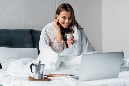 smiling girl with moka coffee looking at laptop in bed in the morning