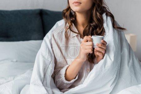 Foto de Recortar vista de chica con taza de café en la cama por la mañana - Imagen libre de derechos