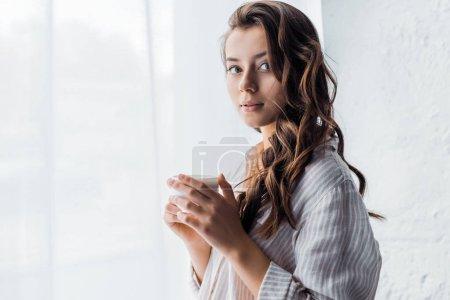 Foto de Hermosa chica morena de pie con taza de café junto a la ventana en la mañana - Imagen libre de derechos