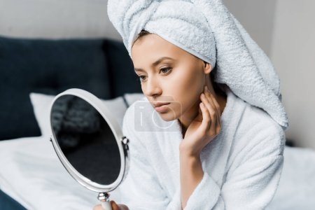 Photo for Beautiful woman in white bathrobe and towel looking at her skin in mirror - Royalty Free Image