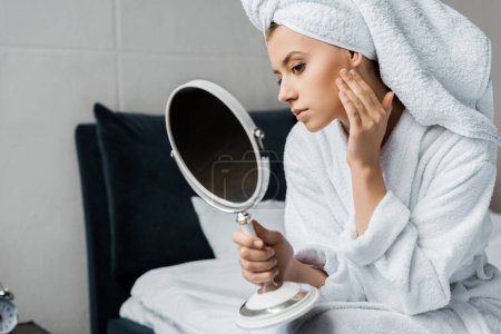 attractive young woman looking at her perfect clean skin in mirror