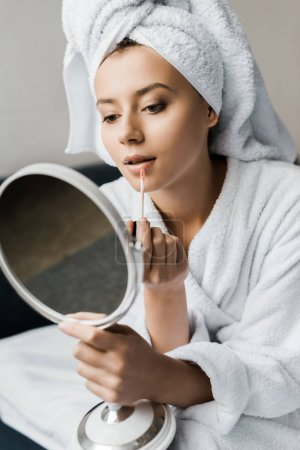 attractive girl in bathrobe applying lip gloss and looking at mirror