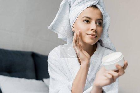 Photo pour Attrayant jeune femme en peignoir et serviette sur la tête appliquer crème hydratante sur le visage - image libre de droit