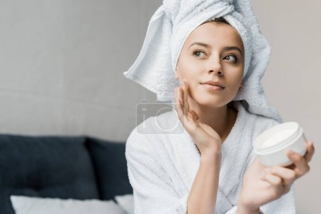 Photo for Beautiful girl with towel on head applying cosmetic cream on face - Royalty Free Image