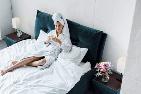 Photo for Beautiful girl in bathrobe and white towel holding cup of coffee in bedroom in the morning - Royalty Free Image