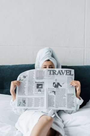 Photo for Young woman hiding behind travel newspaper in the morning - Royalty Free Image