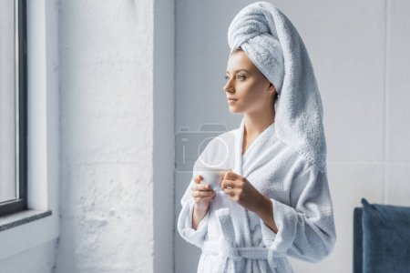 young woman in bathrobe and white towel on head holding cup of coffee and looking at window