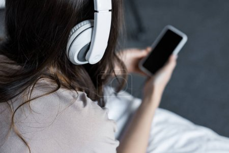 cropped view of girl listening music with headphones and smartphone