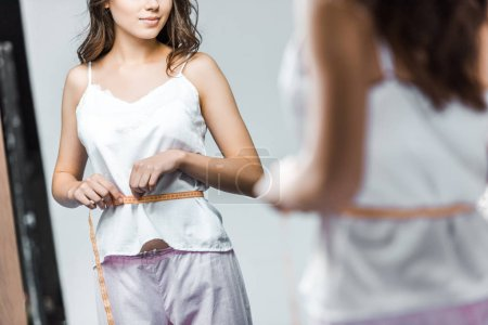 cropped view of woman measuring her waistline and looking at mirror