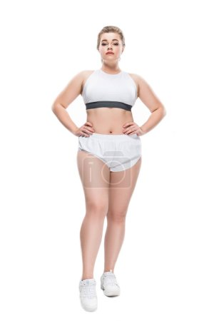 full length view of young size plus woman in sportswear standing with hands on waist and looking at camera isolated on white