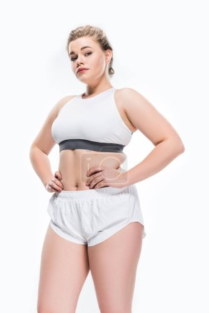 low angle view of young overweight woman in sportswear standing with hands on waist and looking at camera isolated on white