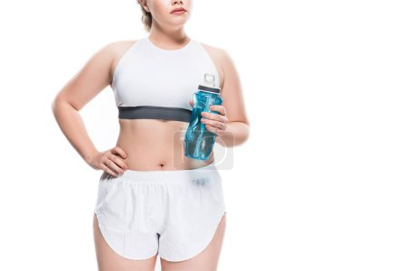 cropped shot of oversize girl in sportswear holding bottle of water isolated on white