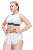 low angle view of young overweight woman in sportswear standing with hands on waist isolated on white