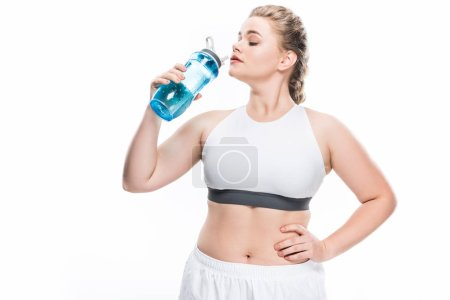 young overweight woman in sportswear drinking water isolated on white