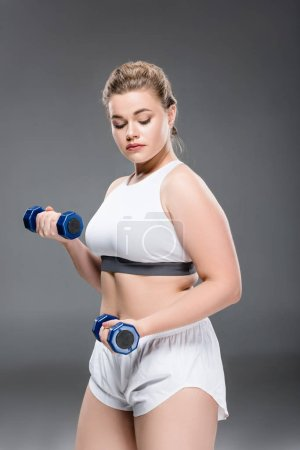 young size plus woman exercising with dumbbells and looking down on grey