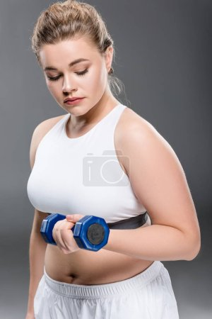young size plus woman exercising with dumbbell isolated on grey