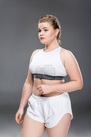 young size plus woman in sportswear standing and looking away on grey