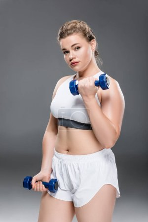 young overweight woman in sportswear exercising with dumbbells and looking at camera on grey