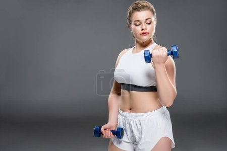 young overweight woman in sportswear exercising with dumbbells on grey